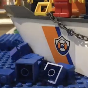 A lego boat moves through lego waters