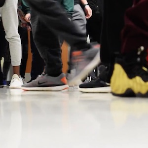 An image that focuses only on the many shoes in a crowded hallway