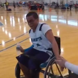 A young man speeds past someone in a wheelchair, ready to play a game of basketball