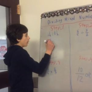 A student works on math problems at a whiteboard