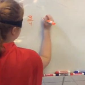 A caped girl works on math at a whiteboard