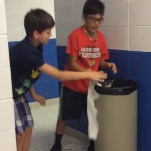 Two boys are excited to throw away trash