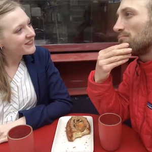 A man and a woman sit at an outside table drinking coffee
