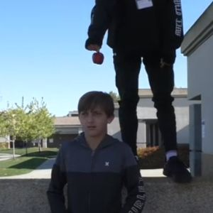 Someone dangles an apple over a boy's head