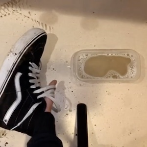 Dirty Vans shoes in front of a bowl of soapy water