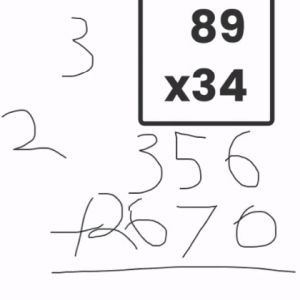 A computer screen shows double-digit numbers multiplied while someone has written, by hand, the multiplication process.