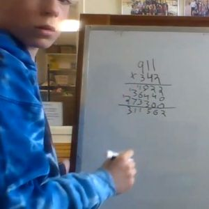Turning from a whiteboard, someone shows large numbers multiplied together.