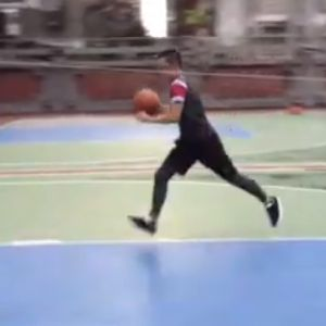 Someone runs down a basketball court with a ball ready to make a shot
