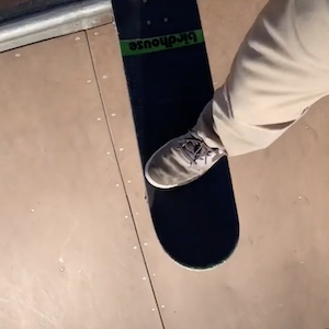 At the top of a ramp, a foot rests at the top of a skateboard with nothing underneath it