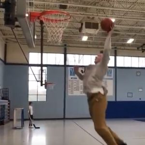 A man flies up to dunk a basketball through a hoop