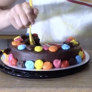 A spoon digs into a half-eaten chocolate cake with colorful frosting dotted across it