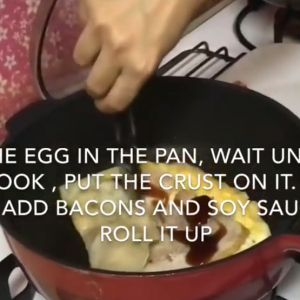 A hand rolls up a thin omelette in a pan