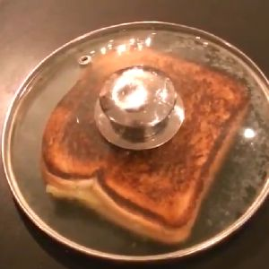 A glass lid covers a grilled cheese sandwhich