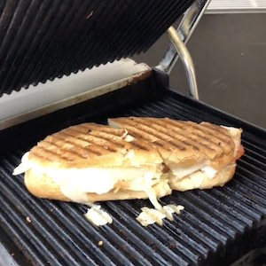 Dark grill lines cross a sandwich that is so full meat spills out onto the grill