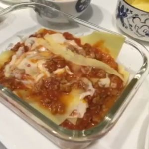 Lasagne is in a glass baking dish on top of an oven