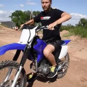 A man sitting on a dirt bike, getting ready to explain the different parts