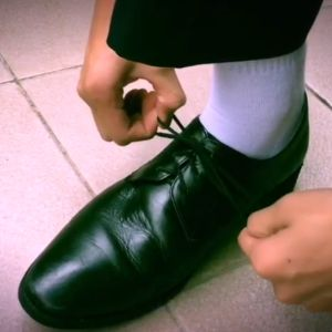 A black dress shoe is tied tightly and correctly