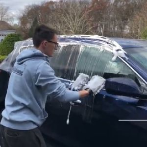 A man uses both hands in soapy sponges to wash a car