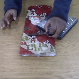 Gift wrap, scissors, and tape are gathered together in order to prepare for wrapping a DVD