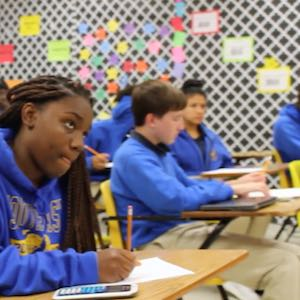 A class of students dressed in light blue shirts and sweatshirts works on the day's lesson, looking intently toward the front of the room.