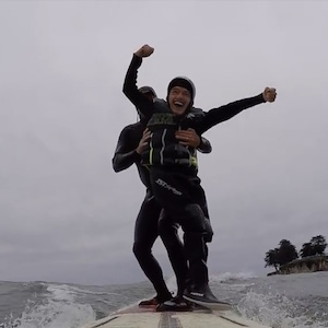 Galen, a student in an adaptive surf camp, stands triumphantly on a surfboard, holding his arms high and smiling as big as he can.