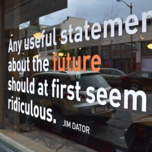 A store-front window displays a quotation about the future