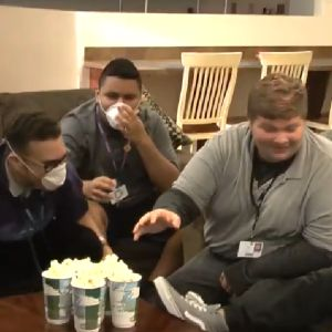 A group gathers around several cups of popcorn, some with masks covering their mouths and noses