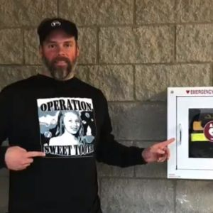 A man points at both an emergency defibrillator and his Operation Sweet Tooth sweatshirt