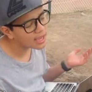 A boy sits on the ground with his laptop and talks about what causes him stress