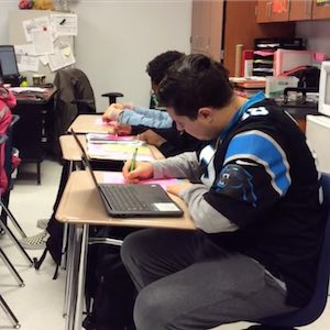 A student sitting at a desk working with a computer out to help him focus