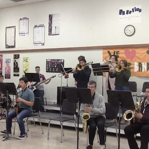 A high-school band room, mostly brass instruments with a bass guitar