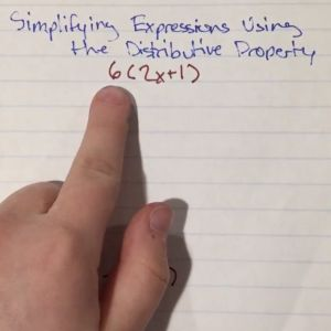 A finger points to a math problem on a piece of binder paper