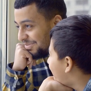 A man and a boy both rest their chin on their hands and stare out the window