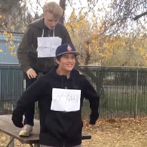 One boy stands on a park bench to get onto another boy's shoulders