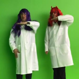 A person with purple hair and another with red hair stand against a green screen with white lab coats