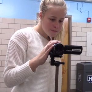 A girl puts a video camera in just the right spot