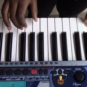 A hand hovers above a keyboard, playing a song
