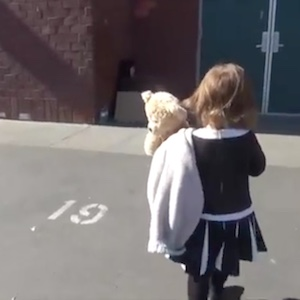 A young girl walks across a parking lot holding a blanket and a teddy bear.